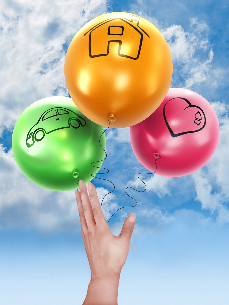 Hand releasing balloons with house, car and heart symbols.